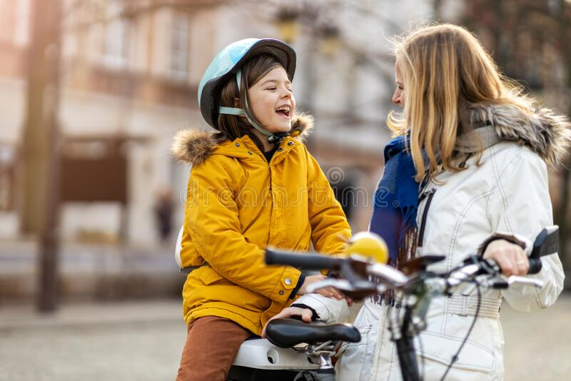 Madre e suo figlio che vanno in bicicletta in città immagini stock