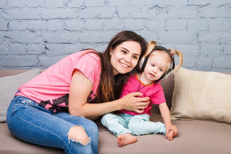 Madre e una figlia di due anni che ascoltano la musica con le cuffie sulla loro testa Sieda sullo strato nella stanza contro immagine stock libera da diritti