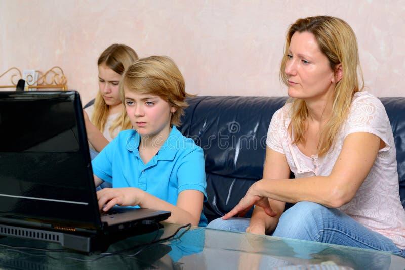 Madre ed i suoi bambini che per mezzo del computer fotografie stock libere da diritti