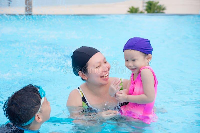 Madre ed i suoi bambini felici nella piscina fotografia stock