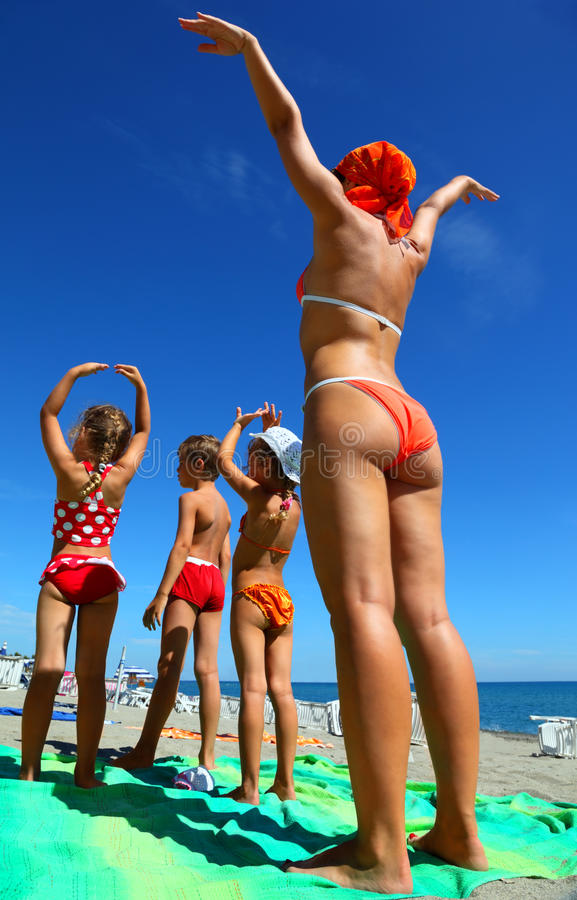 Madre ed i suoi bambini sulla spiaggia fotografie stock