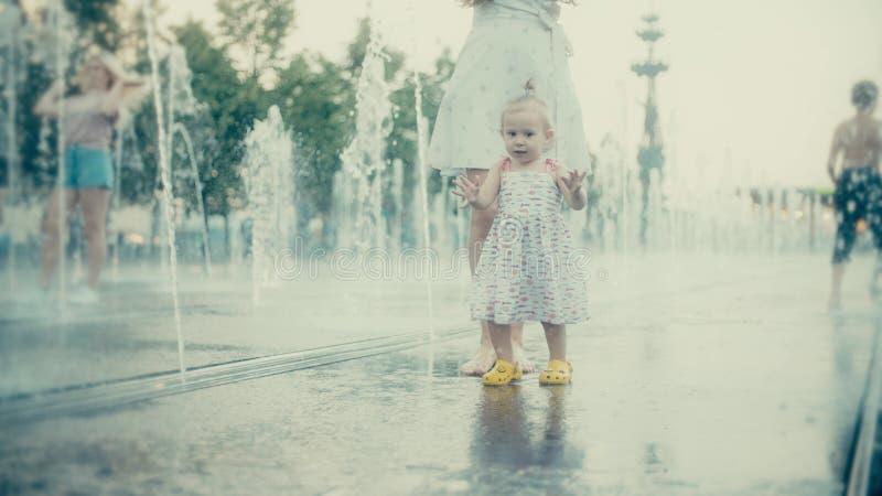 Madre ed il suo piccolo bambino divertendosi in fontana del parco della città, movimento lento immagini stock libere da diritti