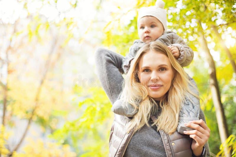 Madre ed il suo piccolo gioco della figlia che stringono a s? sulla passeggiata di autunno in natura all'aperto fotografie stock