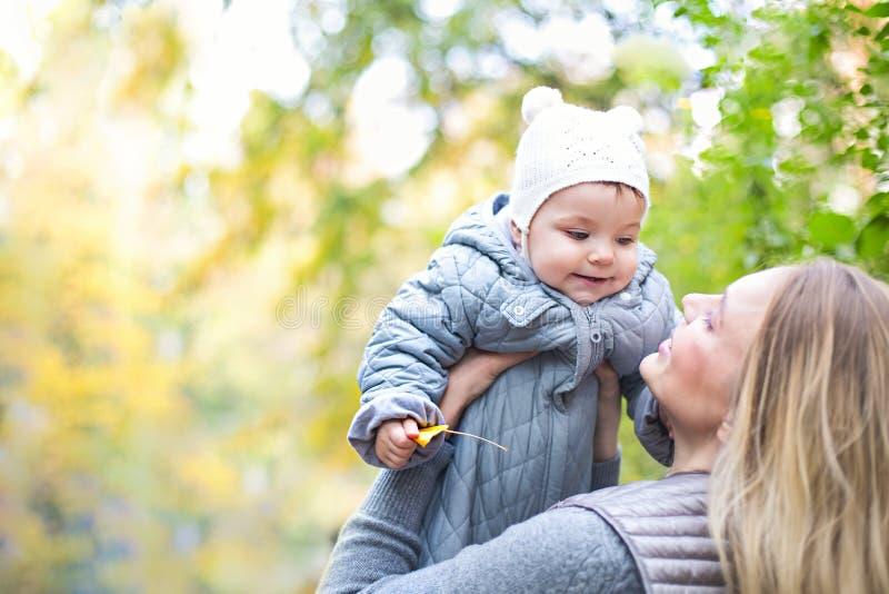 Madre ed il suo piccolo gioco della figlia che stringono a s? sulla passeggiata di autunno in natura all'aperto immagini stock libere da diritti