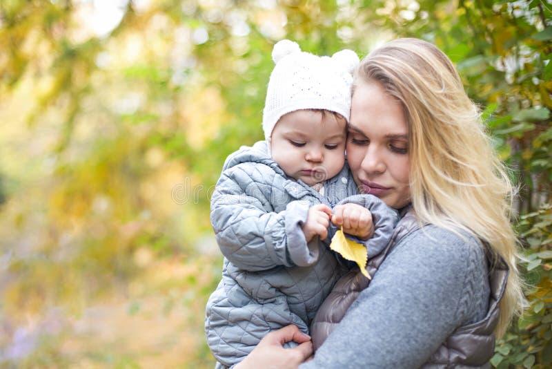 Madre ed il suo piccolo gioco della figlia che stringono a s? sulla passeggiata di autunno in natura all'aperto fotografie stock libere da diritti