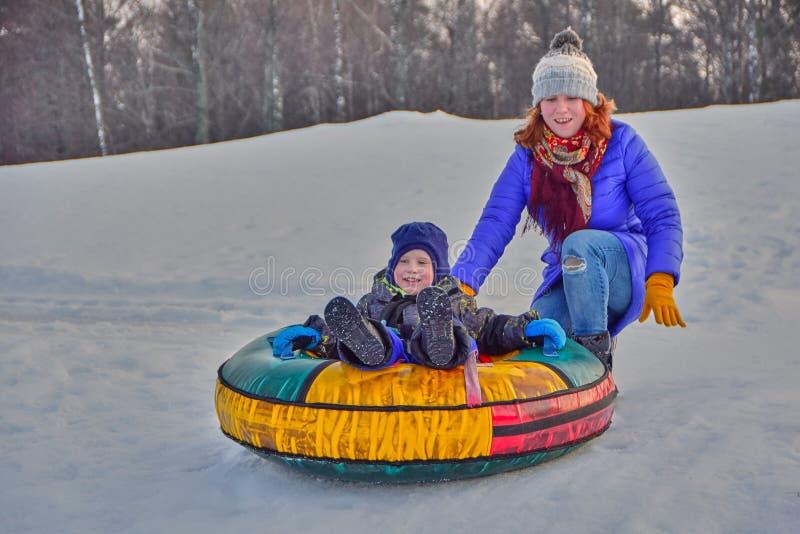 Madre ed suo figlio che godono del giro della slitta fotografie stock
