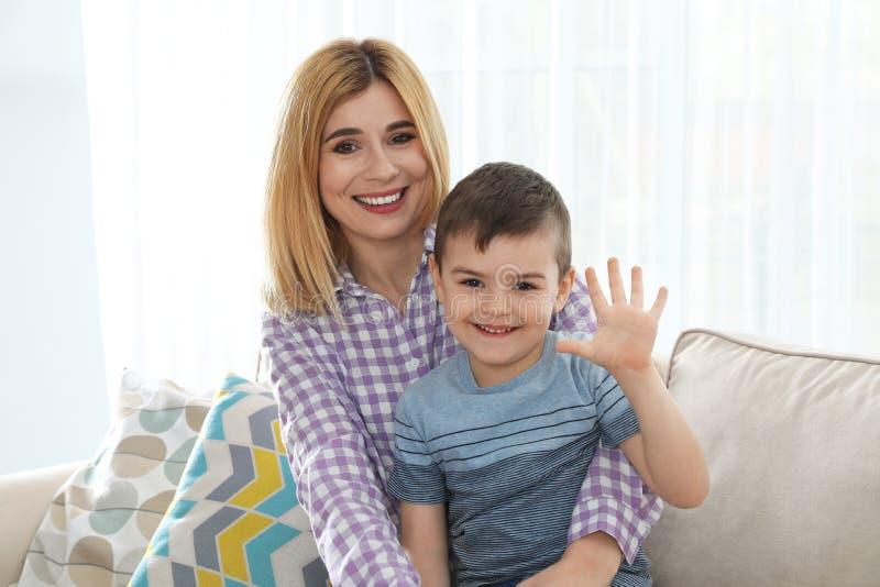 Madre ed suo figlio che usando video chiacchierata contro il fondo leggero fotografia stock