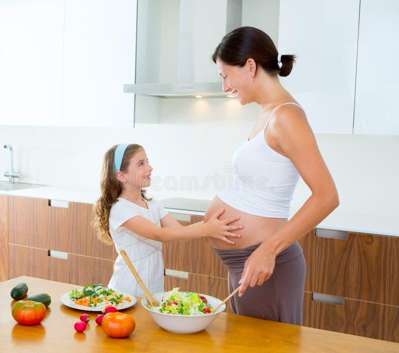 Madre embarazada con su hija en la cocina imagen de archivo