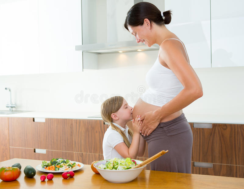 Madre embarazada con su hija en la cocina fotografía de archivo libre de regalías