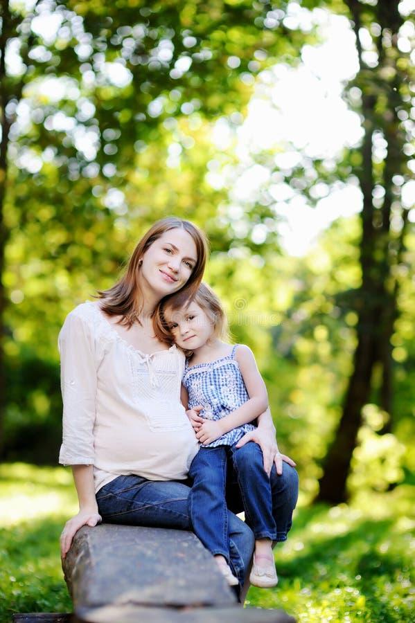 Madre embarazada con su pequeña hija imagen de archivo libre de regalías