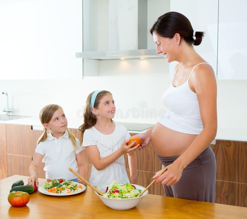 Madre embarazada con sus hijas en la cocina imagenes de archivo