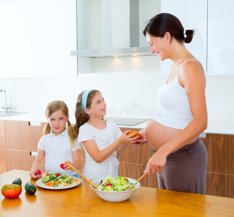 Madre embarazada con sus hijas en la cocina imagen de archivo