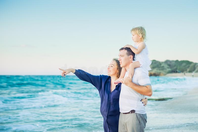 Madre embarazada, padre e hija de la familia feliz abrazándose y mirándolo a continuación al mar durante paseo en la playa Re imagen de archivo libre de regalías