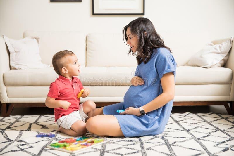 Madre embarazada que pasa tiempo con el hijo en sala de estar imagen de archivo