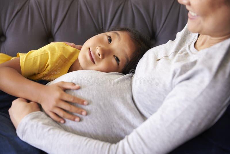 Madre embarazada que se relaja en Sofa With Daughter imágenes de archivo libres de regalías