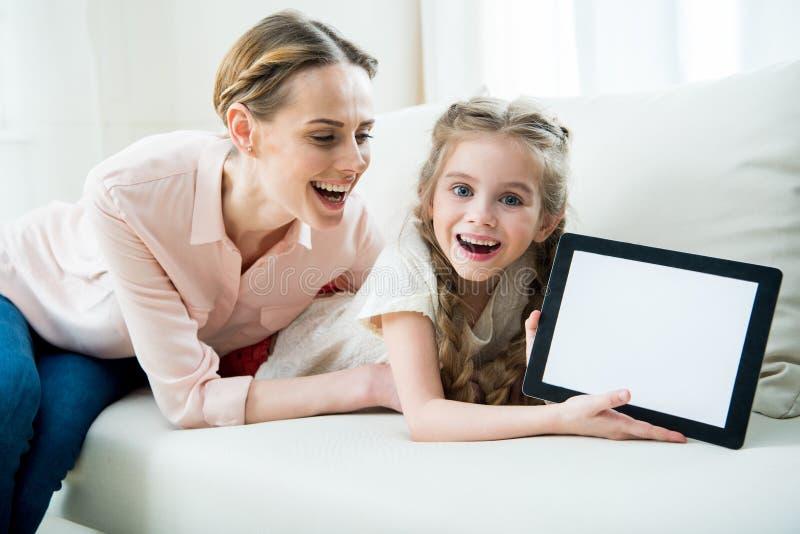 Madre emocionada e hija que muestran la tableta digital fotos de archivo