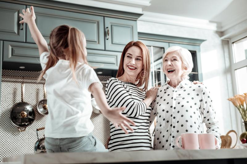 Madre emocionada y abuela que parecen impresionadas mientras que mira a la muchacha fotografía de archivo libre de regalías