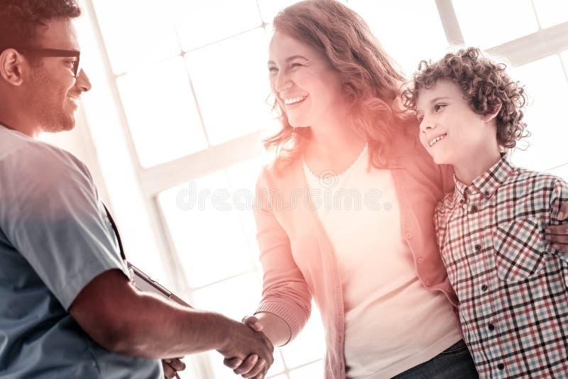 Madre emocionada y doctor alegre que sacuden las manos imagenes de archivo