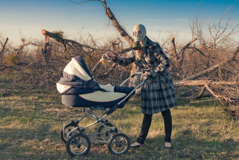 Madre en careta antigás con el cochecillo de bebé fotos de archivo