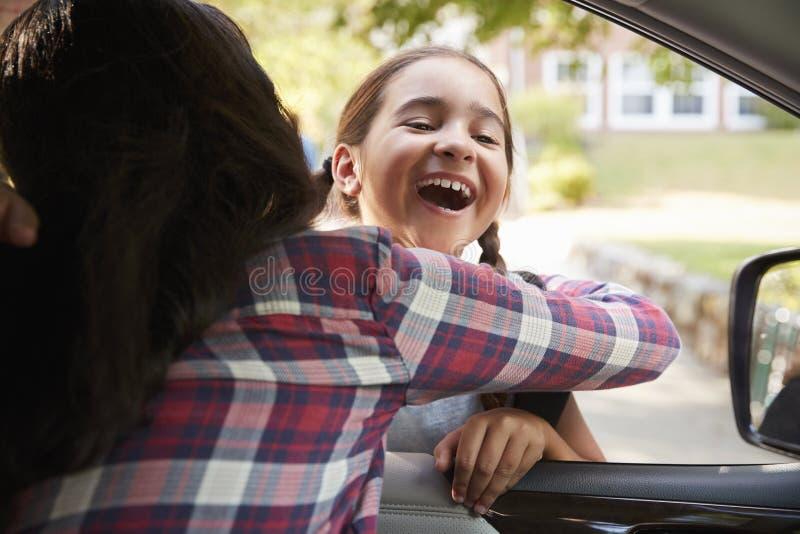 Madre en coche que recoge a la hija en Front Of School Gates fotografía de archivo libre de regalías