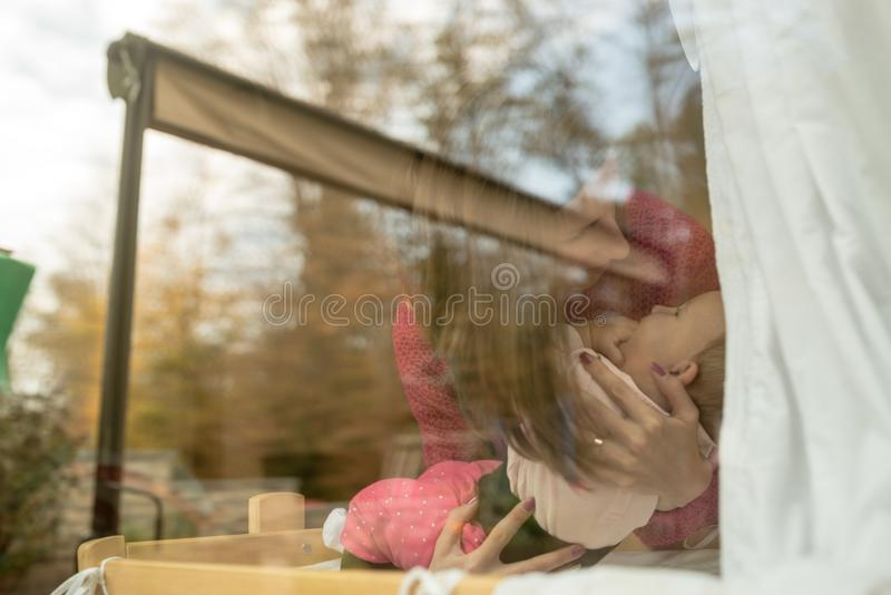Madre en el jersey rosado que detiene a un bebé dentro en casa fotos de archivo libres de regalías