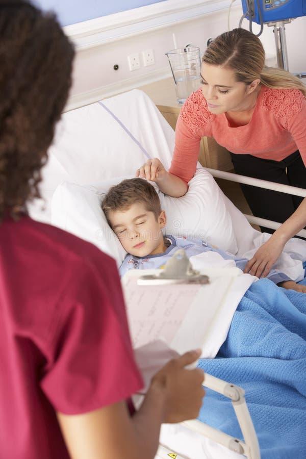 Madre en la cabecera del hijo con la enfermera en hospital imagen de archivo libre de regalías