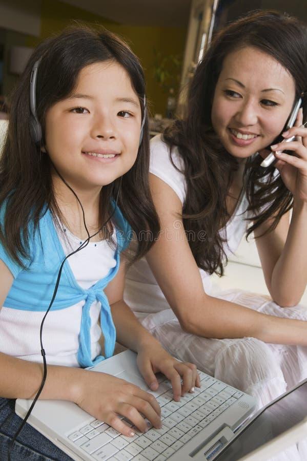 Madre en la hija de observación del teléfono celular que usa el ordenador portátil en retrato de la sala de estar fotografía de archivo libre de regalías