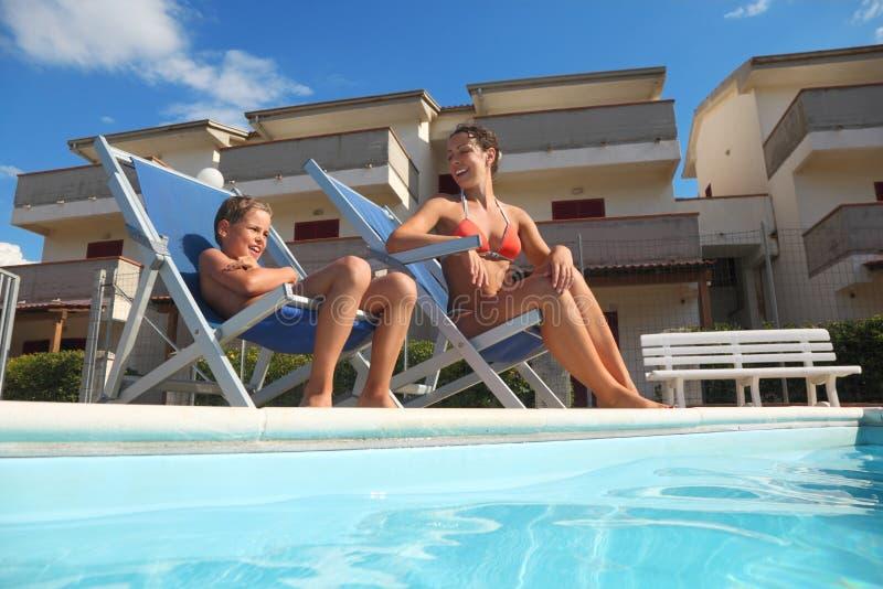 Madre en pareo e hijo que se sienta en silla de playa fotografía de archivo