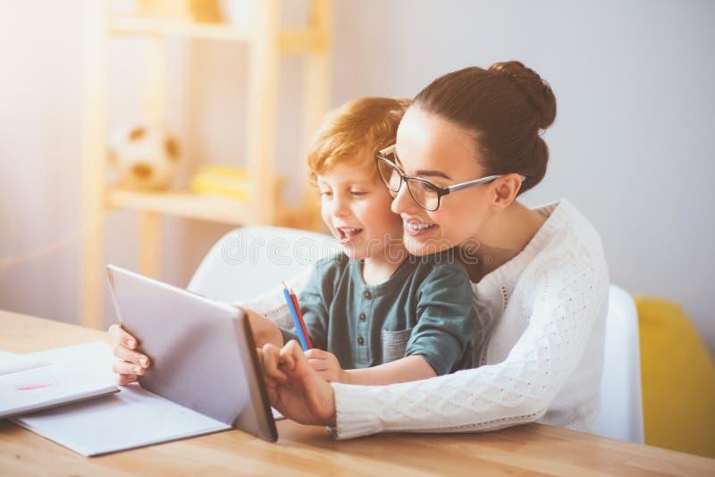 Madre encantada que enseña a su hijo que usa una tableta fotografía de archivo