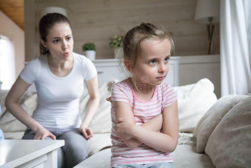 Madre enojada que regaña a la pequeña hija preescolar triste fotos de archivo