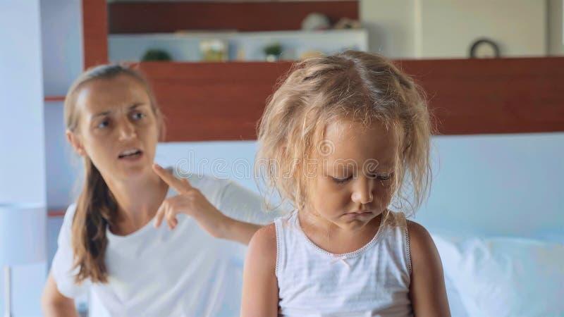 Madre enojada que regaña a su hija mientras que se sienta en la cama en dormitorio en casa fotos de archivo