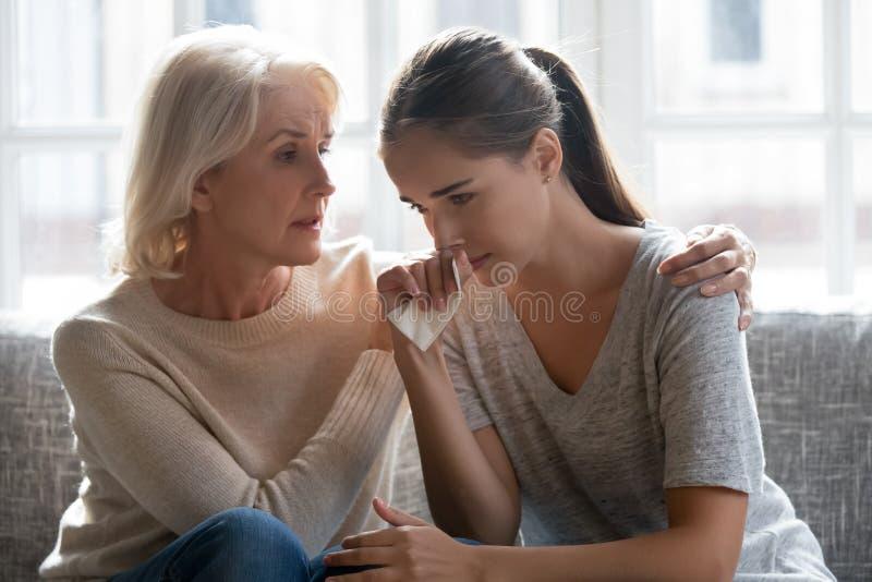 Madre envejecida de amor calmar a la familia adulta de la hija que se sienta en el sofá imagenes de archivo