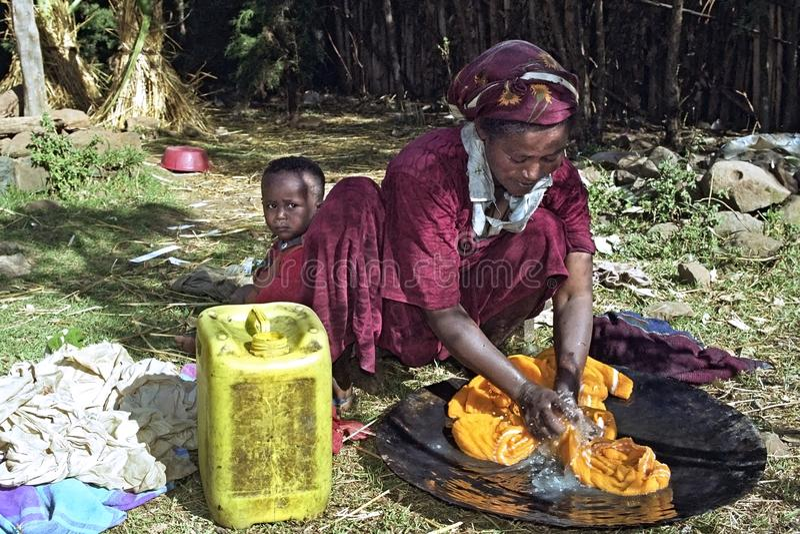 Madre etiopica con la lavanderia di lavaggio del bambino a casa fotografie stock