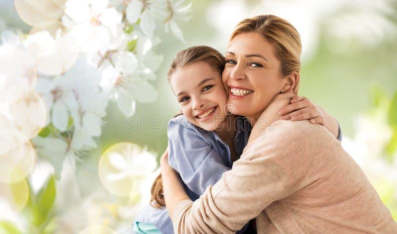Madre felice che abbraccia figlia sopra il fiore di ciliegia fotografia stock