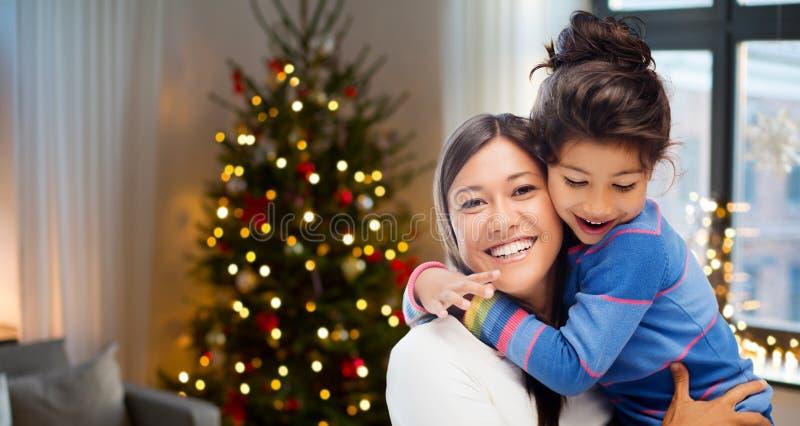 Madre felice che abbraccia sua figlia su natale immagini stock