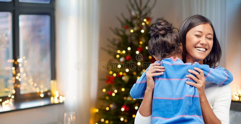 Madre felice che abbraccia sua figlia su natale immagine stock libera da diritti