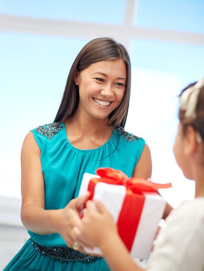 Madre felice che dà regalo di compleanno al suo bambino fotografia stock