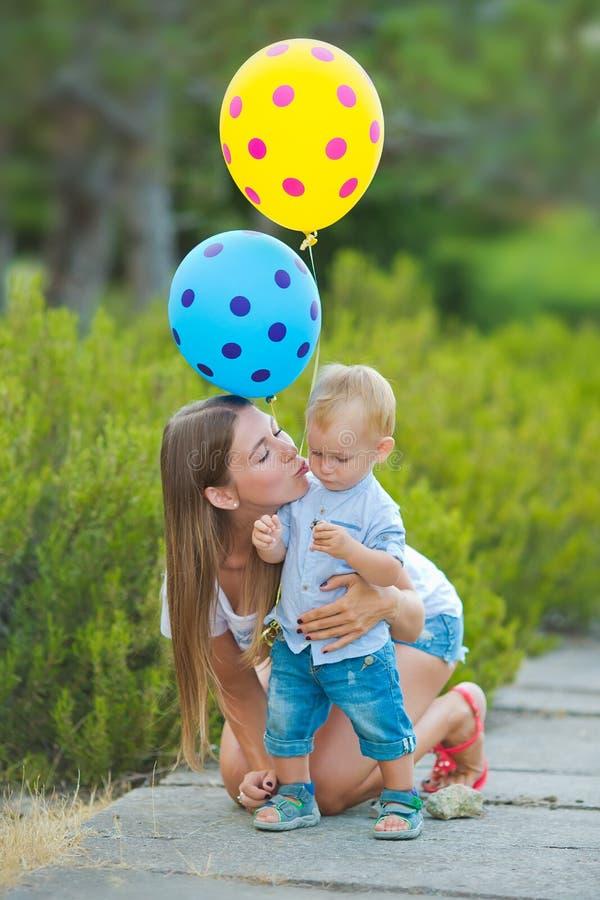 Madre felice che gioca con suo figlio nel parco fotografie stock