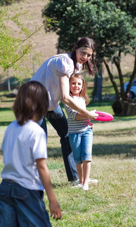 Madre felice che gioca Frisbee con i suoi bambini immagine stock