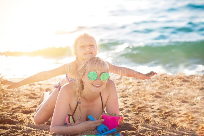Madre felice che riposa sul mare con sua figlia fotografia stock libera da diritti