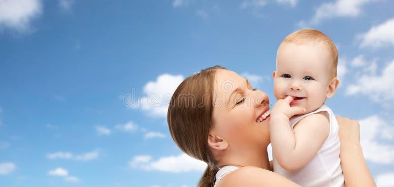 Madre felice che tiene bambino adorabile sopra cielo blu immagine stock libera da diritti