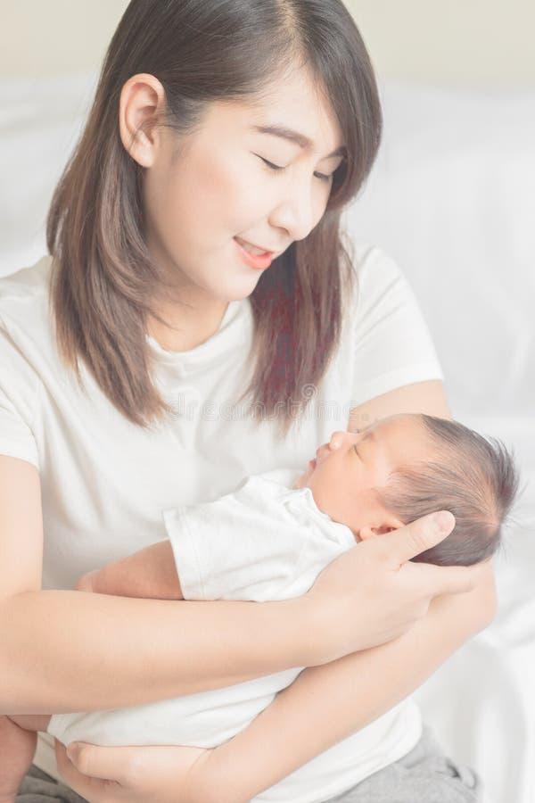 Madre felice che tiene il bambino adorabile del bambino fotografia stock