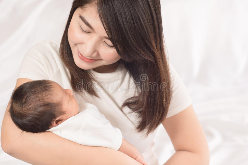 Madre felice che tiene il neonato adorabile del bambino fotografie stock libere da diritti