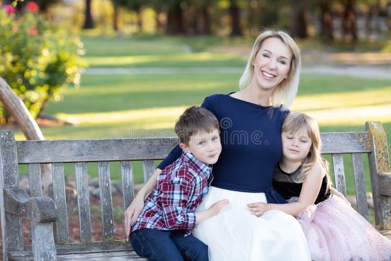 Madre felice con due bambini che si siedono su un banco di legno in un giardino immagine stock