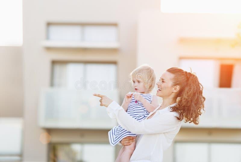 Madre felice con il bambino che sta davanti alla costruzione di casa immagini stock