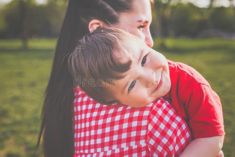 Madre felice con il bambino divertendosi all'aperto fotografia stock