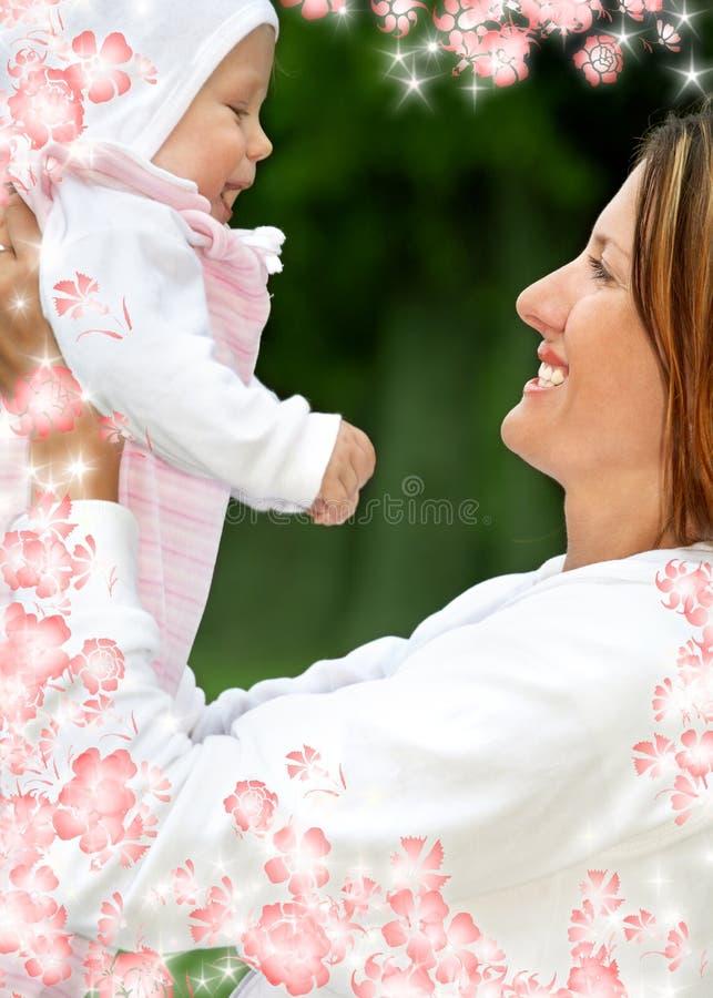 Madre felice con il bambino ed i fiori fotografia stock libera da diritti