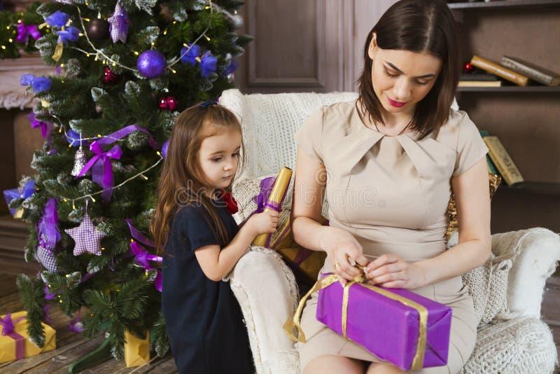 Madre felice con la figlia che avvolge i regali di Natale a casa immagine stock