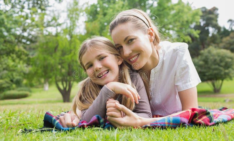 Madre felice con la figlia che si trova al parco fotografia stock