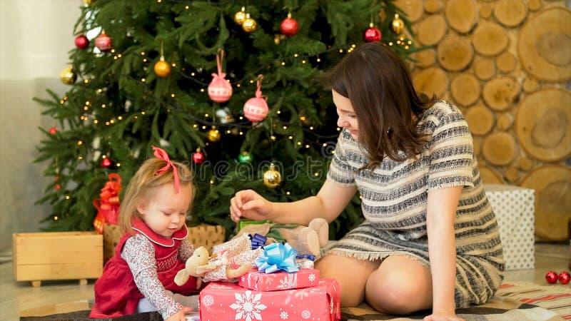 Madre felice con la sua piccola figlia che gioca vicino all'albero di Natale Bella madre che gioca con la sua piccola figlia fotografia stock